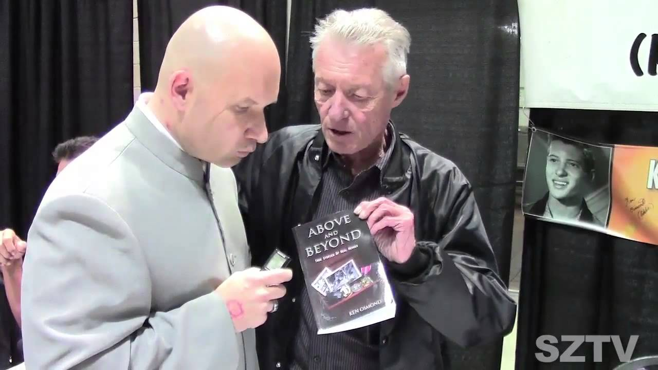 Ken Osmond with a book in his hand. He is telling someone about the book.