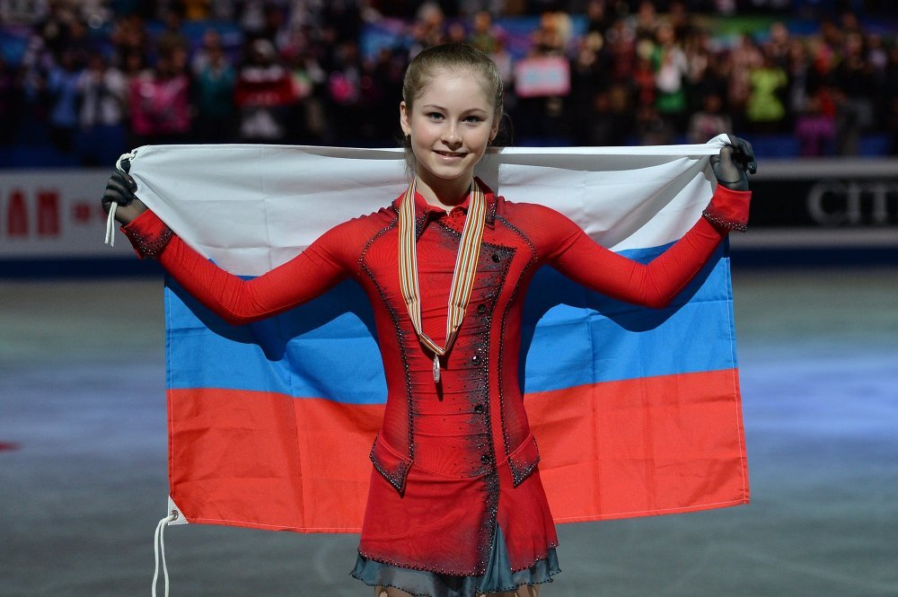 15-year-old Yulia Lipnitskaya holds the Russian flag with the gold medal on her neck in the 2014 Olympics.