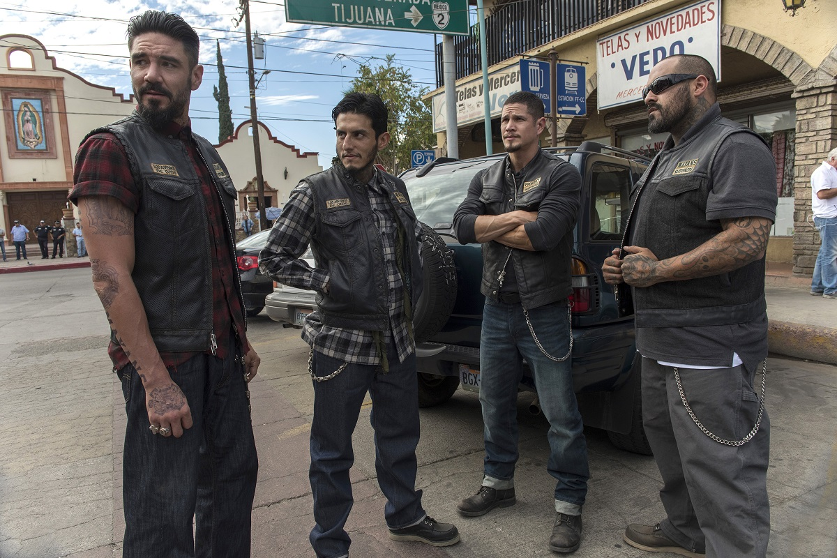 Mayans MC actors standing. Everyone is wearing half leather jacket