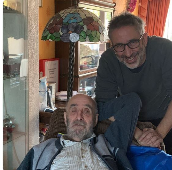 Dr. Colin Baddiel with his son David Baddiel. Colin Baddiel is resting on the couch where as his son his standing behind him.
