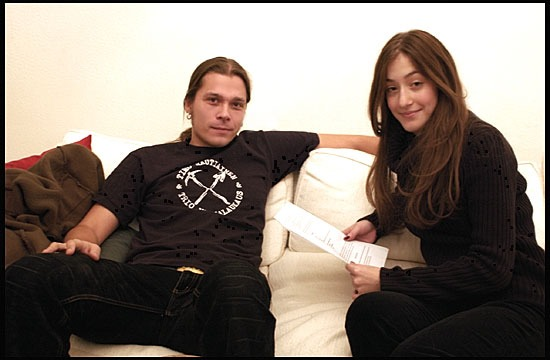 Sandra Mittica is sitting beside Finnish singer Emerson Burton on a sofa.