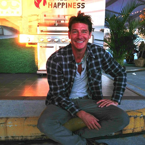 Ty Pennington sitting in the side of the road with his hand in his lap