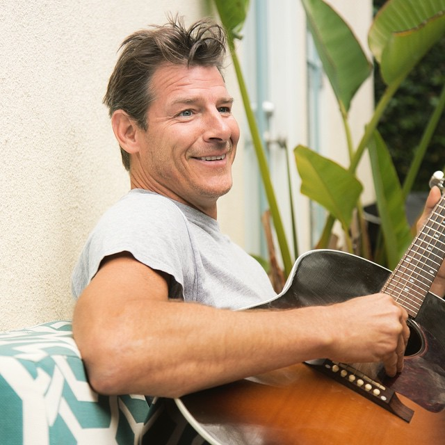Ty Pennington smiling while he plays the guitar.