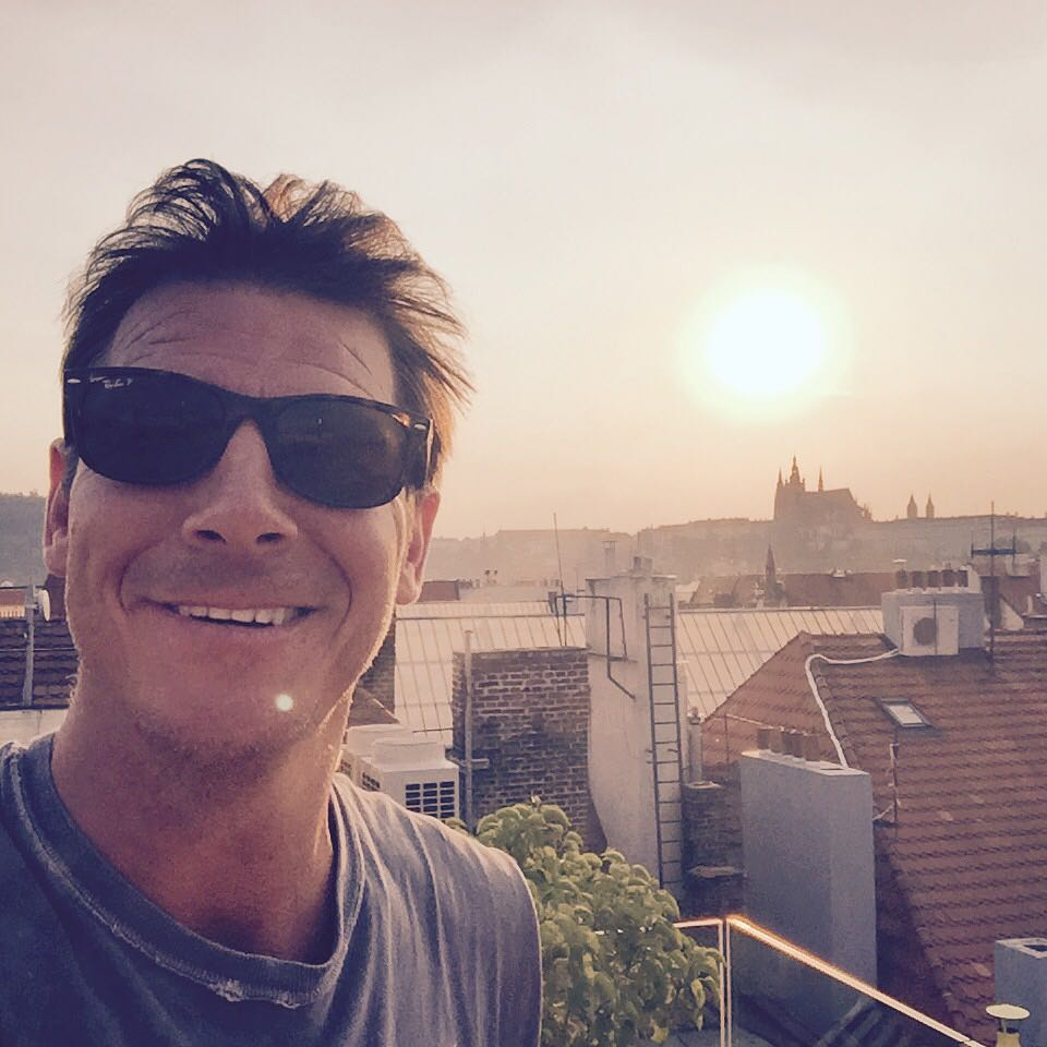Ty Pennington wearing black sunglasses in the sun while smiling for a selfie.