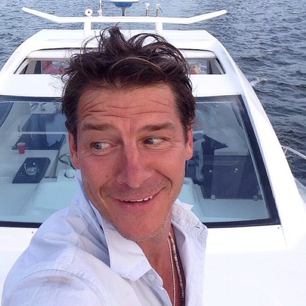 Ty Pennington looks towards the left and takes a selfie in a boat.
