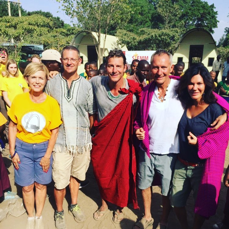 Ty Pennington smiling for a photo with the community people of Tanzania and associates.