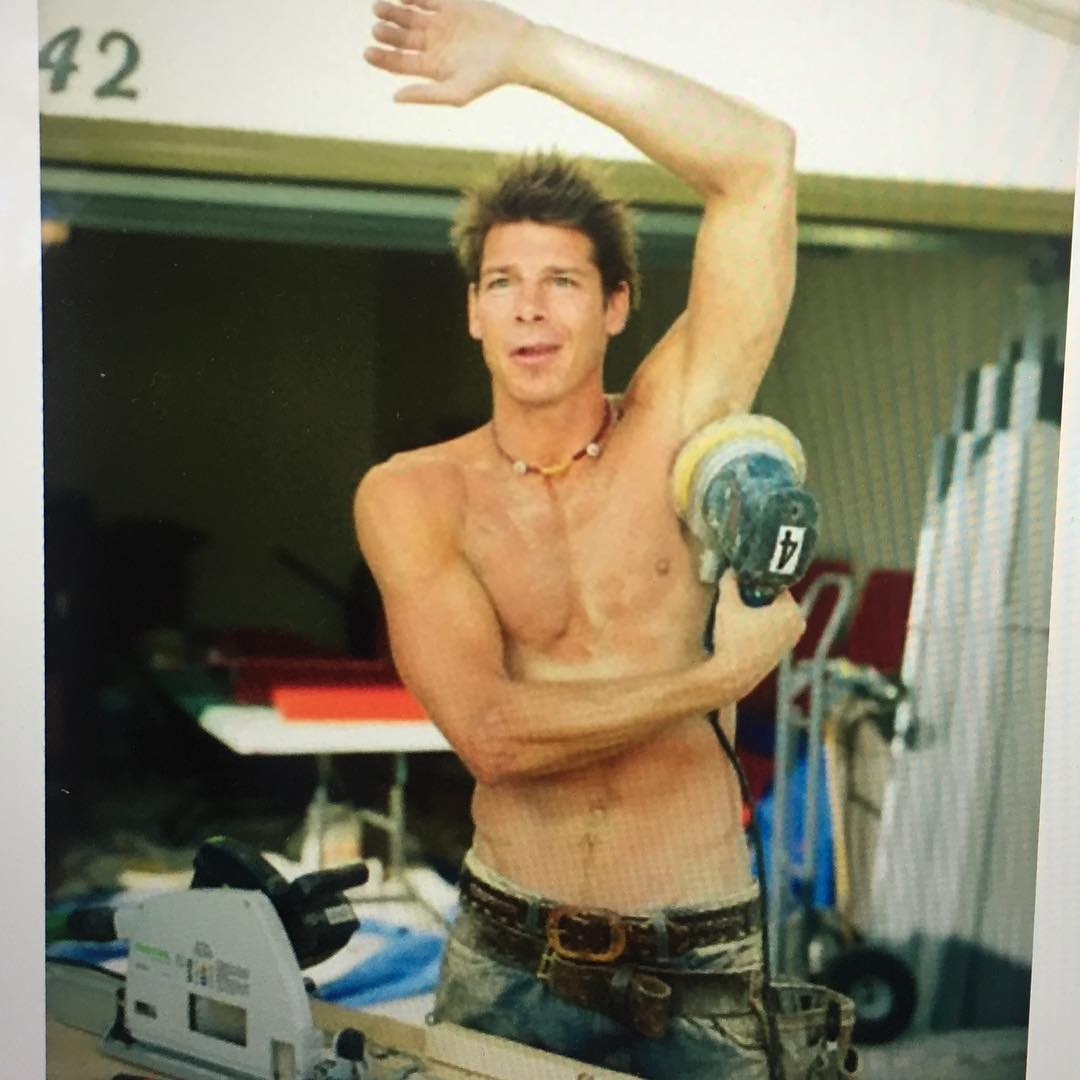 Ty Pennington posing in a funny stance with one hand in the air and another holding a power tool