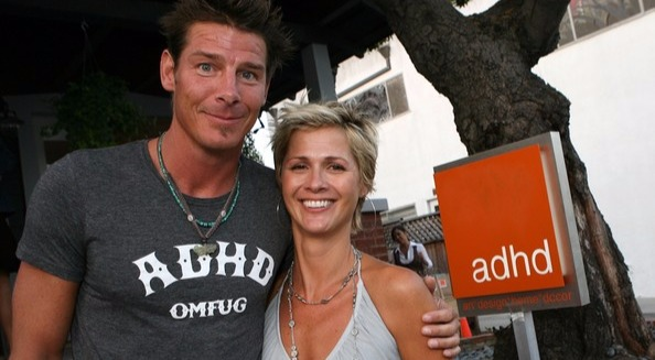 Ty Pennington hugs his girlfriend Andrea Bock with one hand and smiling.