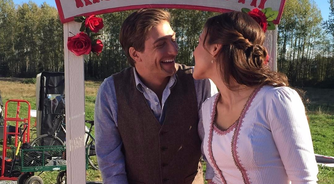 Daniel Lissing and Erin Krakow standing at a booth, cozying up to each other