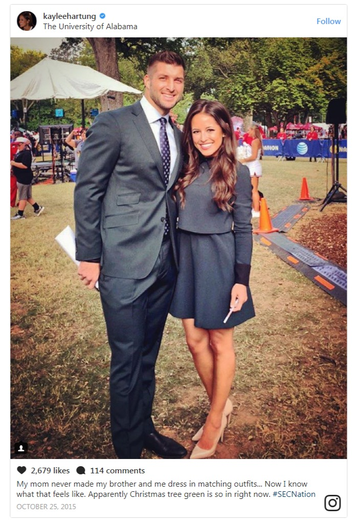 Kaylee Hartung and Tim Tebow are wearing the same grey colored dress. They are smiling at the camera.
