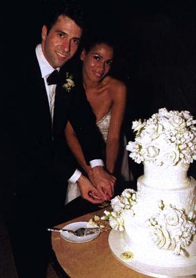 Troy Garity and his wife Simone Bent cutting their wedding cake on their wedding day.