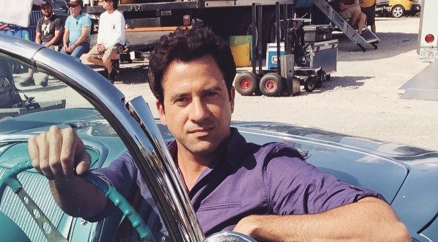 Troy Garity during his series, Ballers' premier year. He is riding a car in a purple colored shirt.