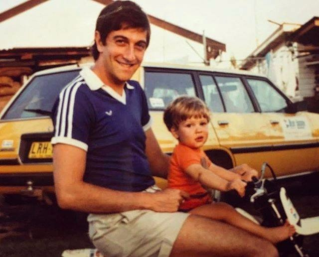 Young Daniel Lissing and his father are riding on a bike. There's a yellow car in the background.