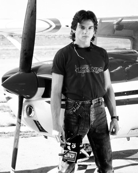 The young Jason Gedrick poses on a photoshoot for the classic movie Iron Eagle. Jason has tucked his black t-shirt inside his jeans. Jason is standing in a stylish pose infront of an airplane.