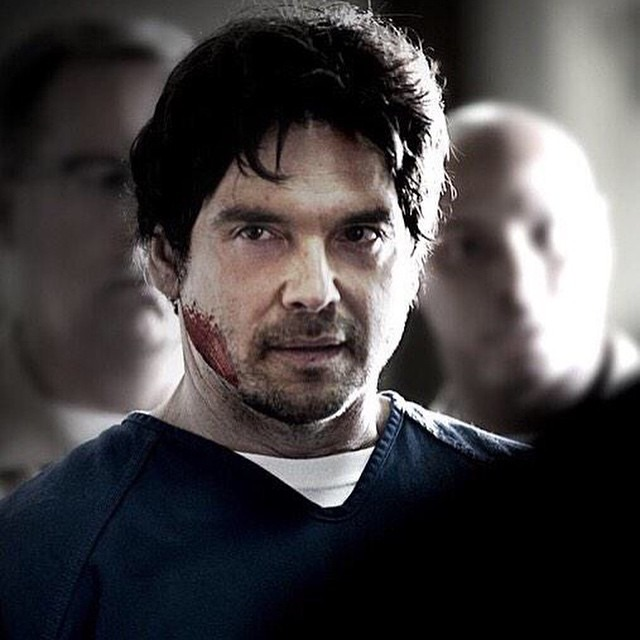 Jason Gedrick is looking away from the camera. He is wearing a blue t-shirt. He has a blood on his right cheek.