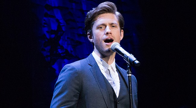 Aaron Tveit with an open mouth, he's standing in front of a mic