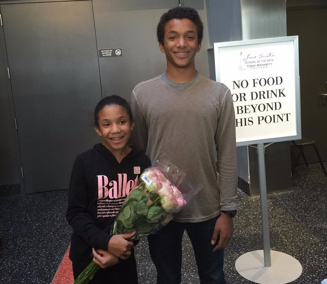 Sunny Hostin's son Gabriel is smiling while looking at the camera and daughter Paloma is standing next to her brother with a bouquet of flowers in her hand.