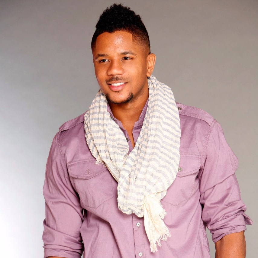 Young Hosea Chanchez wearing light purple shirt. He is also wearing a scarf loosely around his neck and is smiling.