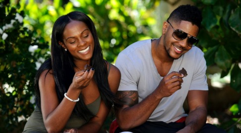 Hosea Chanchez and his ex-wife Tika Sumpter are holding a piece of chocolate in their hand. Both of them are looking at the chocolate and smiling.