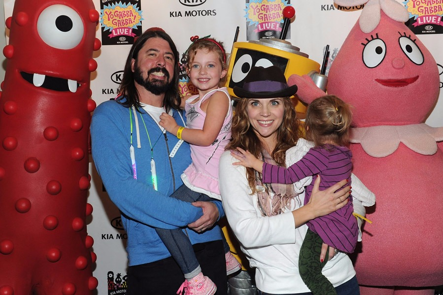Jordyn Blum and husband Dave Grohl carry their daughters in their arm. They all seem in a holiday mood.