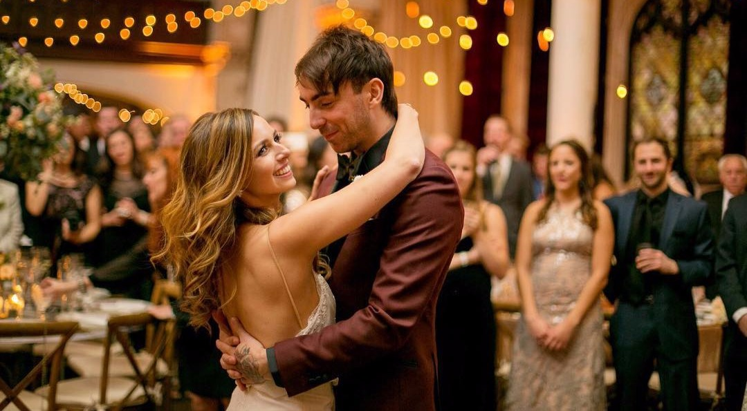 A photo from Alex Gaskarth and Lisa Ruocco's wedding day. People are surrounding Alex and Lisa as they share their first dance. Lisa is looking sideways and Alex is looking at Lisa.
