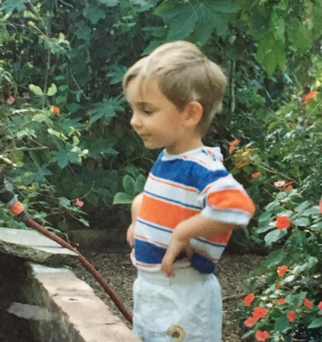 Young Alex Gaskarth is wandering in a garden. He is wearing a white tee-shirt with blue and orange stripes. He is holding her hand to his waist level.
