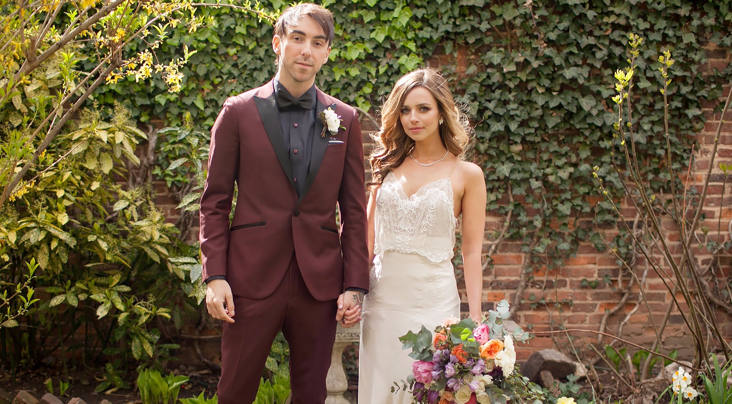Alex Gaskarth and Lisa Ruocco's wedding photo. Alex is in a maroon suit and Lisa is in a white sleeveless gown, holding a bouquet of colorful flowers. They are holding hands.