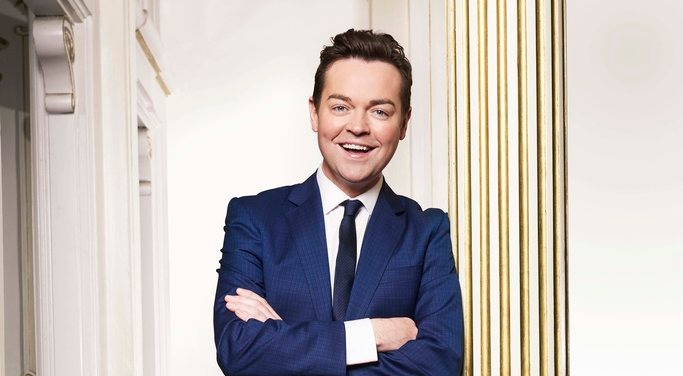 Stephen Mulhern leaning on to a golden pillar