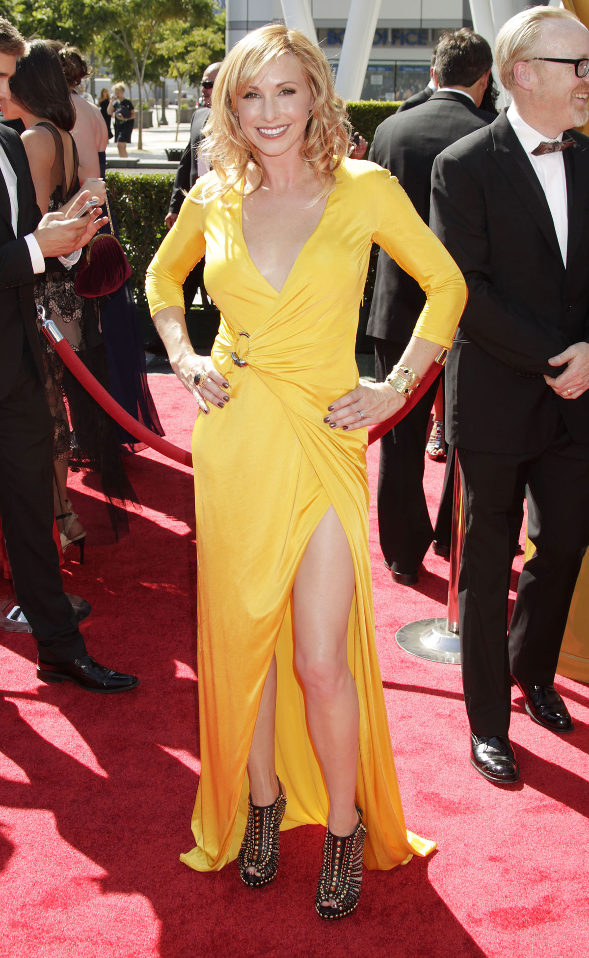 Kari Byron posing for a picture wearing a beautiful yellow dress