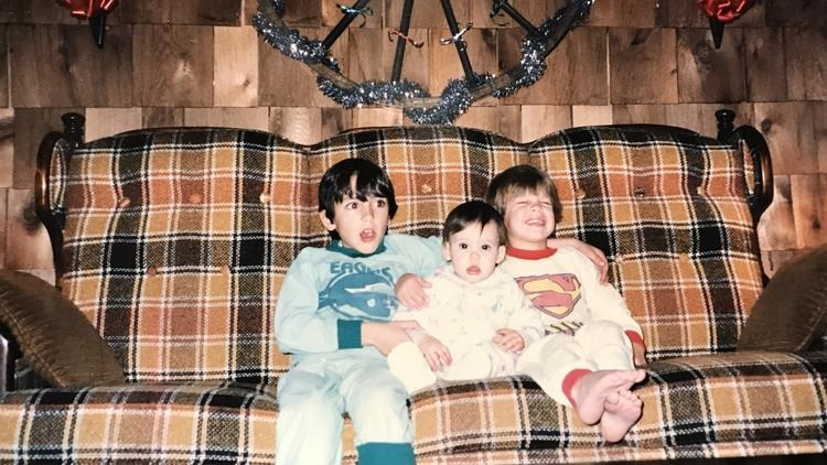 Cheryl Scott (middle) sitting on a couch with her two elder brothers. The young Cheryl is facing the camera while her brothers are making faces.
