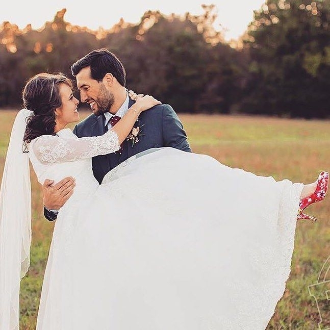 Jeremy Vuolo carrying his newlywed wife Jinger Duggar while posing for a picture on their wedding day.