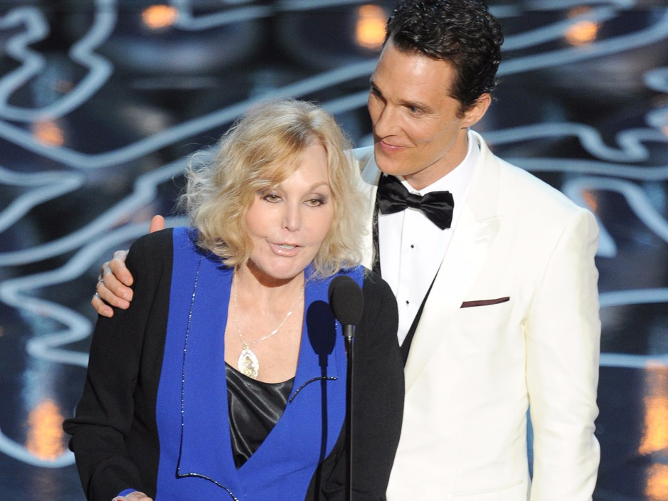 Matthew McConaughey and Kim Novak on the stage of 2014 Oscar. Matthew McConaughey is half-embracing Kim Novak who is talking on a mic.