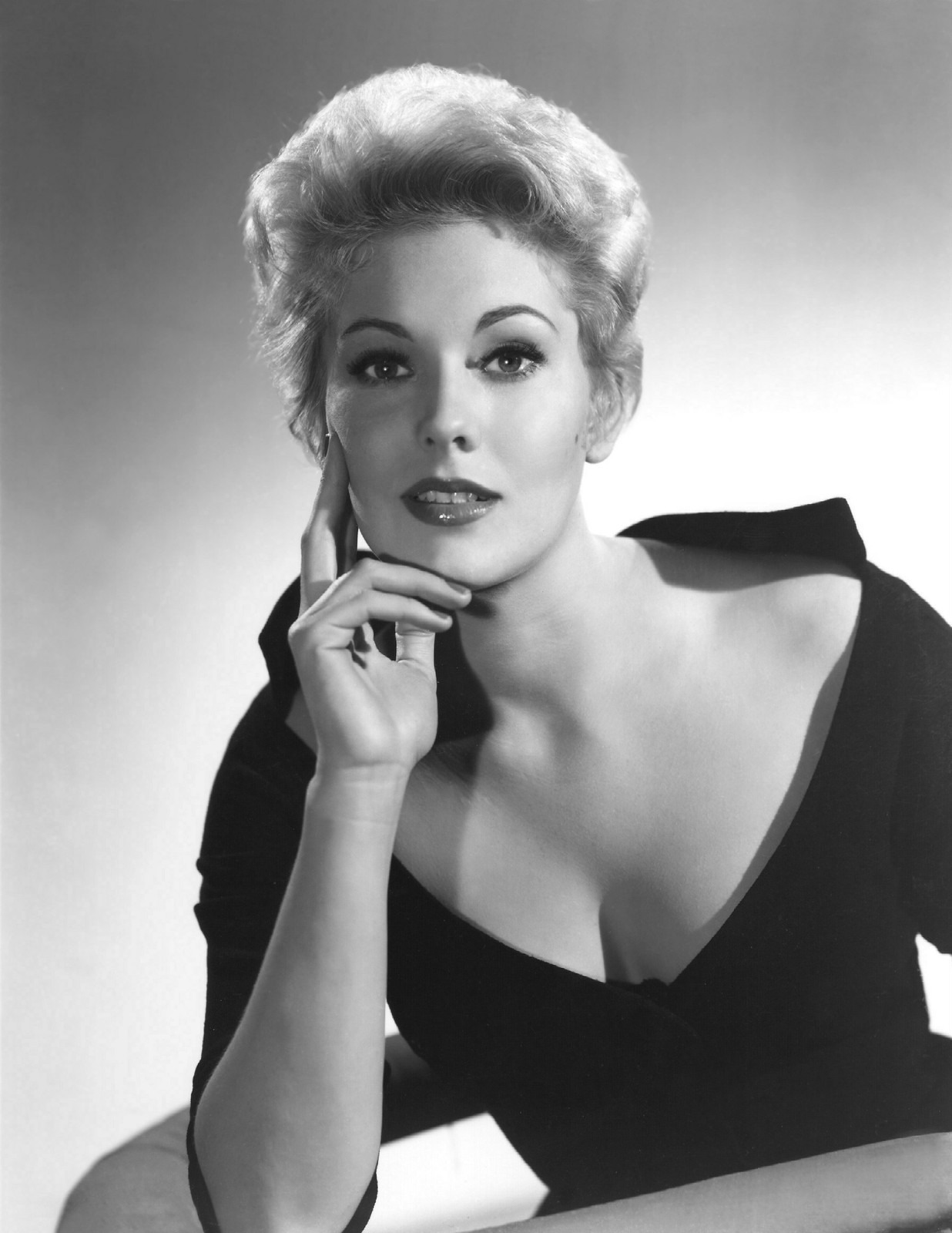 A black and white image of young Kim Novak. She looks really hot in the figure-hugging dress which reveals ample amount of her cleavage.