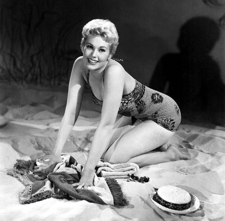 Kim Novak is posing playfully in a bathing suit on a beach.