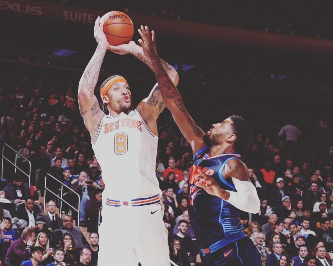Michael Beasley taking a shot as another player attempts to block