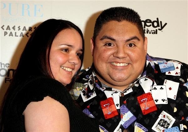 Claudia Valdez and boyfriend, Gabriel Iglesias wearing a smile poses for the camera while Gabriel looks at the camera and Claudia looks away