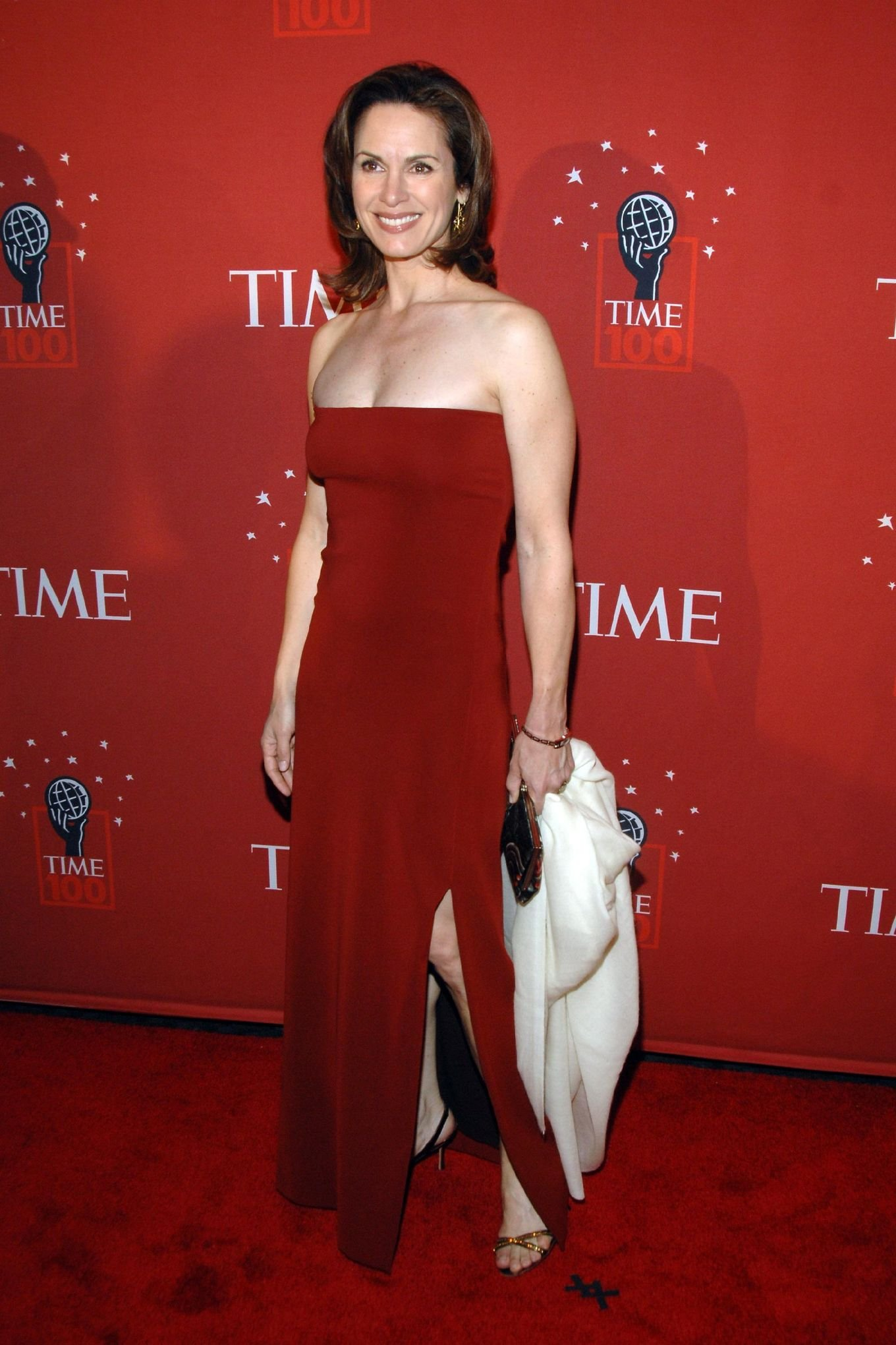 Hot Elizabeth Vargas in a strapless red dress smiling for the camera. She's holding a white piece of cloth in one hand.