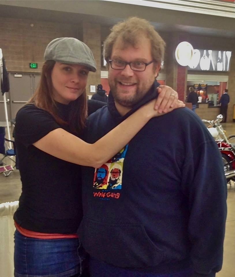 Mikey Teutul is seen with girlfriend/wife Karen Baker at the airport. Karen has wrapped both her arms around Mikey in a loving hug. They are both facing the camera wearing casual tshirt and jeans.