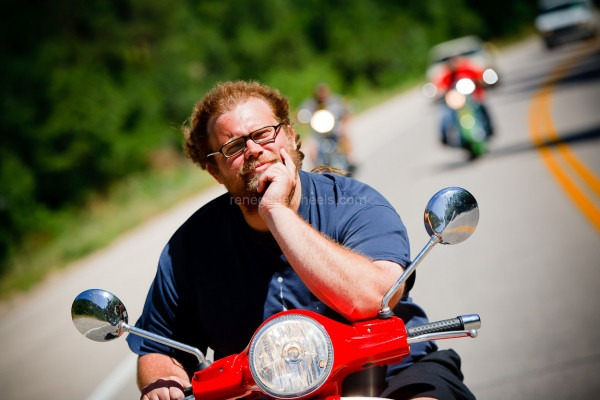 Mikey Teutul is riding on a red motor scooter, hand on his chin and the other on the handle bar. He is wearing a blue tshirt and has a contemplative look on his face.