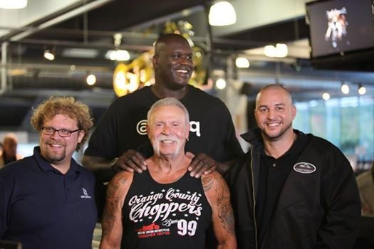 Mikey Teutul is joining in a photo with Paul Sr, Shaquille Oneal and another member of OCC. The OCC members stand side by side with Shaq behind Paul Sr with his hands on Sr's shoulders.