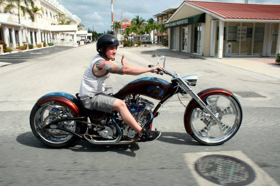 Cody Connelly is sitting on a custom chopper. He is wearing a sleeveless white t-shirt and a half pant. His tattoo is being exposed in his right hand. He is holding the handle of the chopper with his right hand and posing with a thumbs up with his left hand. He is wearing a black helmet and looking away from camera.