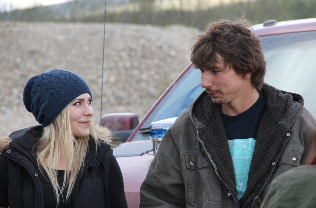 Parker Schnabel is sitting in front of a car with his girlfriend, Ashley. He is wearing a grey jacket and trying to talk. Ashley is wearing a black jacket and a woolen cap. She is looking at Parker with a smile.