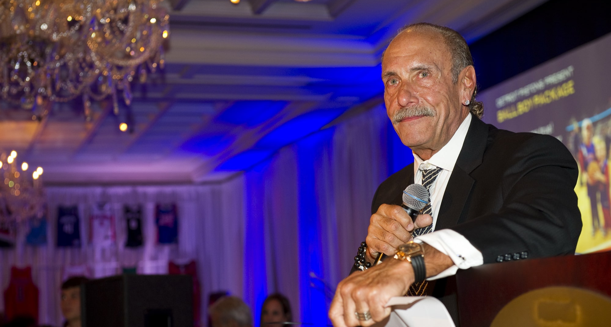 Les Gold is attending an event. He is holding a mic in his right hand. He is looking away from the camera with a subtle smile.