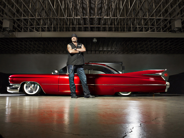 Danny Koker is standing in front of a red car