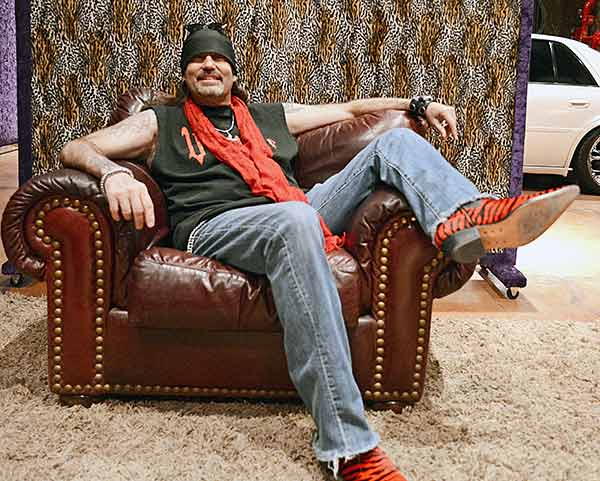 Danny Koker is sitting on a couch