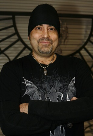 Danny Koker, a Pawn star is facing camera with a smile on his face. He is wearing black T-shirt and black head band. He has folded his hands and is in a good posture.