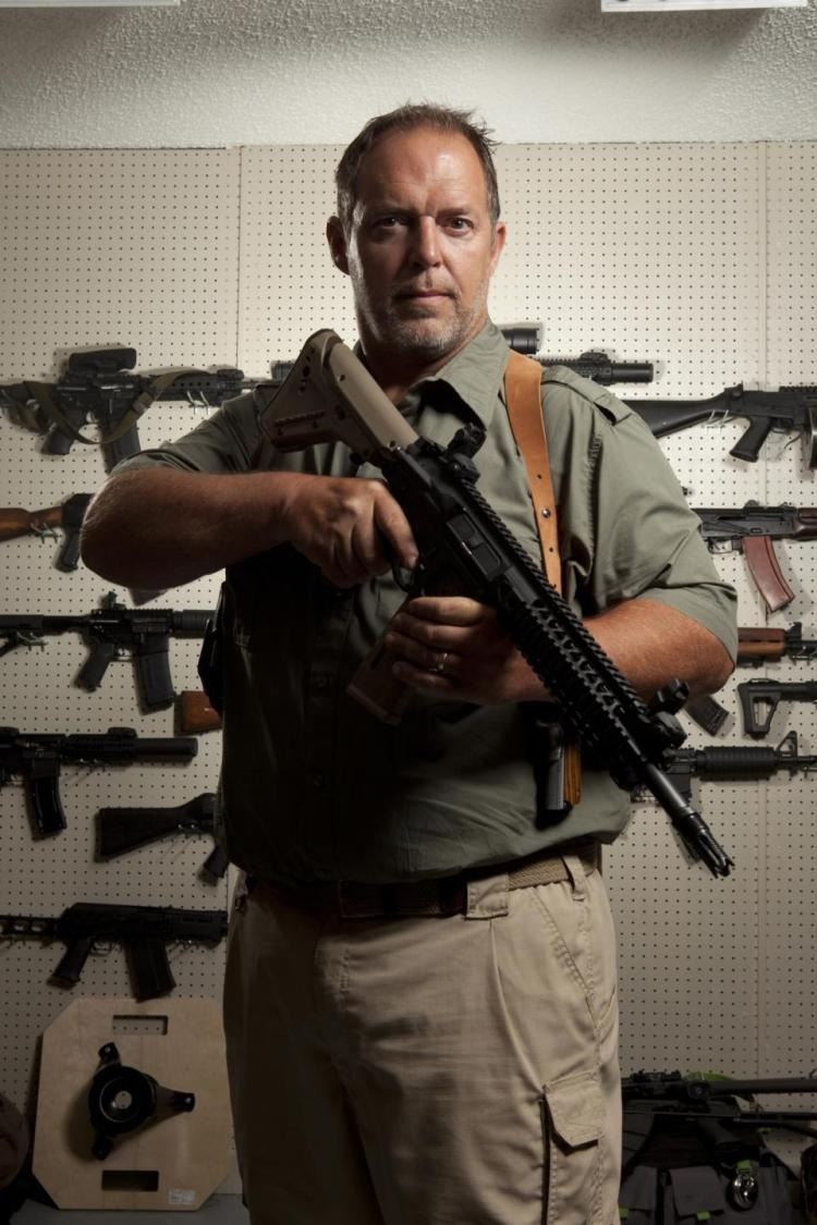 Sons of Guns William Hayden is looking at the camera holding gun in his hands. He is standing in the gun showroom.