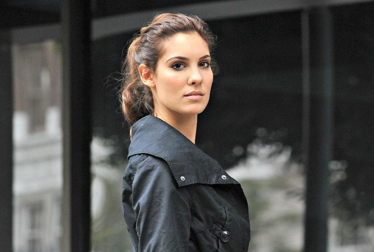 Daniela Ruah is standing sideways with her eyes straight on the camera. She is wearing a black over coat.