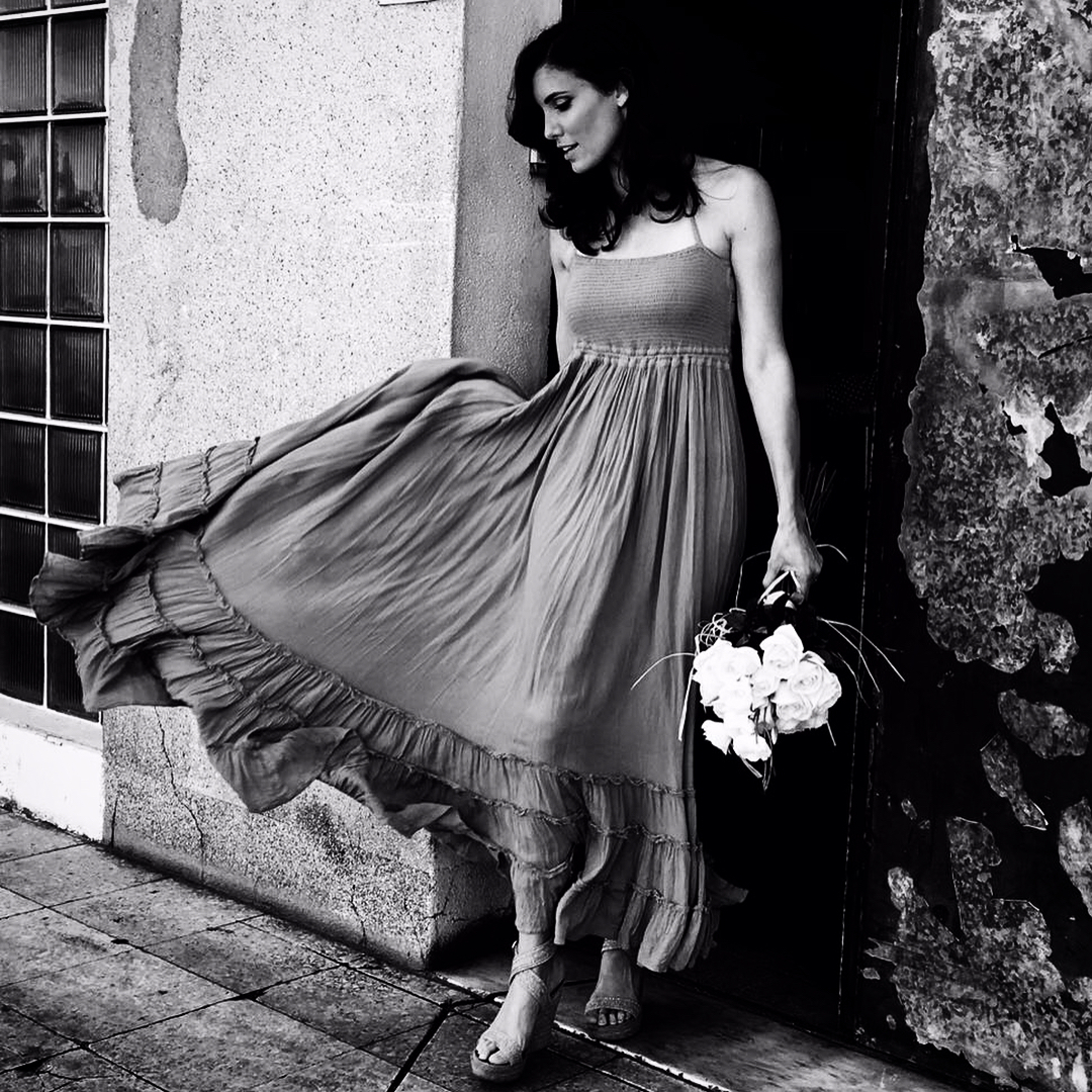 Daniela Ruah is standing on the outdoor. She is holding a flower in her left hand. She is wearing a gown. She is looking away from the camera.