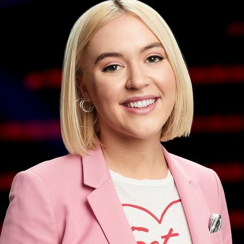 Chloe Kohanski is wearing Pink Blazer. She is looking towards the camera with a beautiful smile. Her blonde hair has added extra beauty to her face.